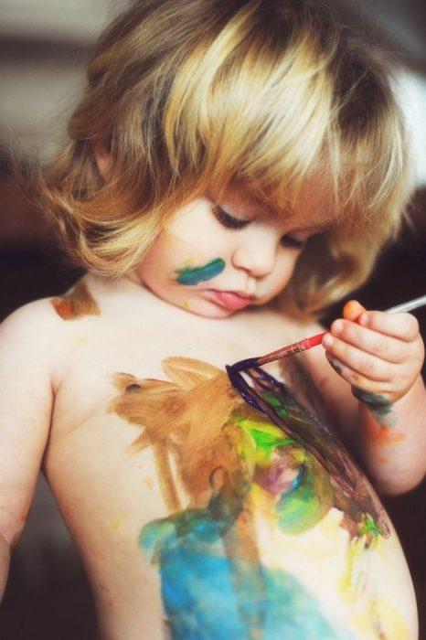 niña pintándose el cuerpo