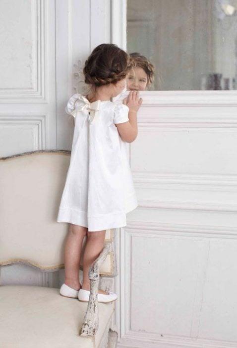 niña mirando su reflejo en el espejo