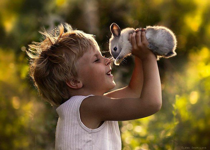 niño jugando con un conejo