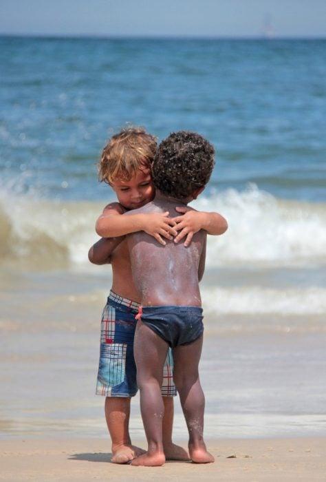niños pequeños abrazándose en la playa