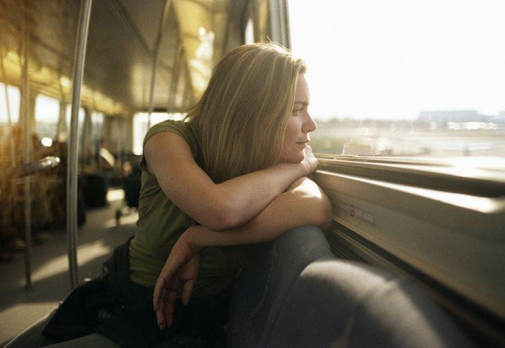 mujer mirando por la ventana de un tren
