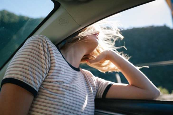 chica con la cabeza fuera de la ventana del coche