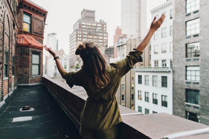 chica con los brazos abiertos en un balcón
