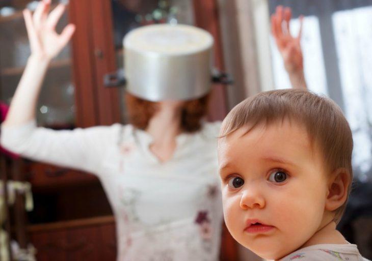 mamá con una olla en la cabeza y bebé volteando a la cámara