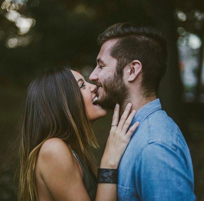 Chica mordiendo la barbilla de un chico mientras ríen felices