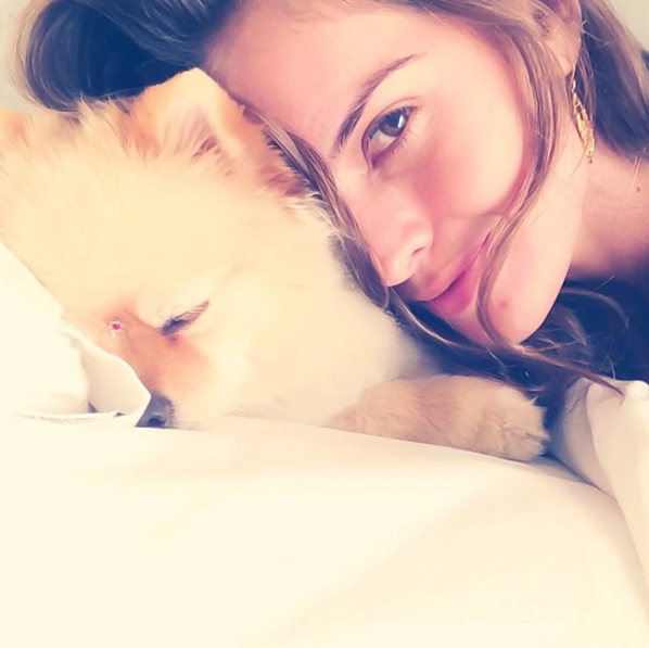 Modelo de victoria secret Izabel Goulart sin maquillaje recostada junto a su cachorro