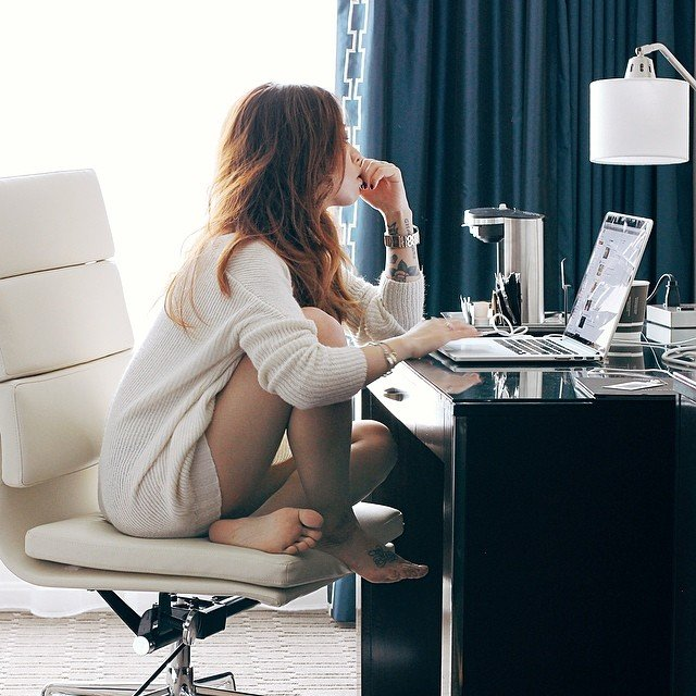 Chica sentada frente a un escritorio revisando su computadora