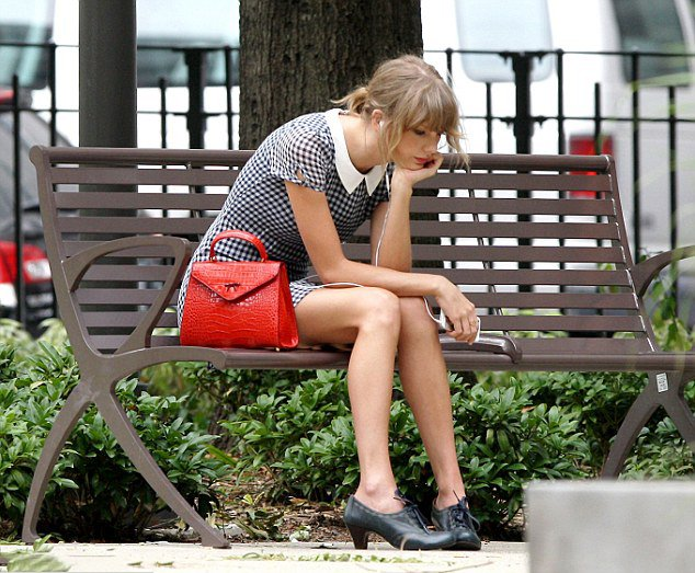 Taylor swift sentada en una banca pensando mientras escucha música