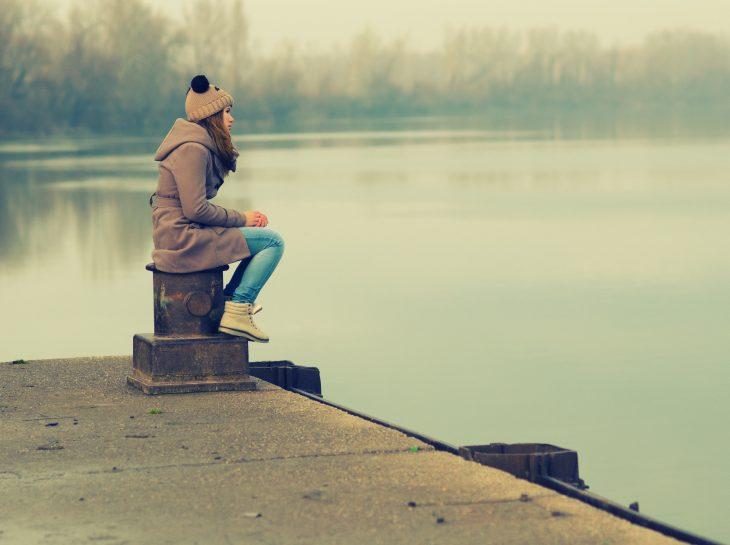 Chica reflexionando a la orilla de un lago