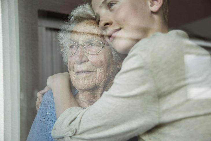 Abuela y nieta abrazadas en la ventana