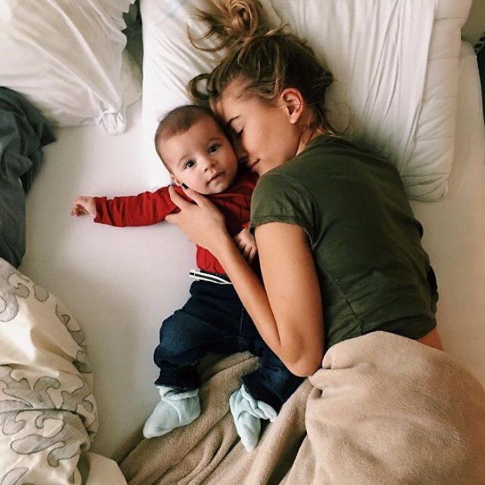 Chica y bebé acostados en una cama