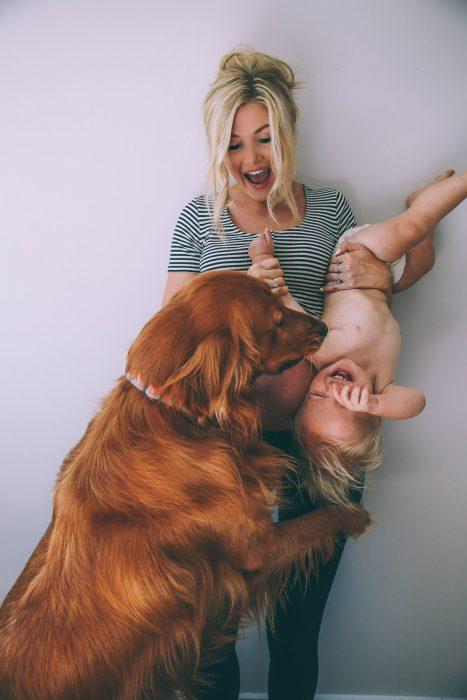 Chica sosteniendo a un bebé de cabeza y jugando con un perro
