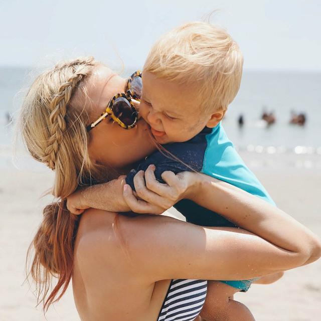 Chica abrazando a un bebé en la playa