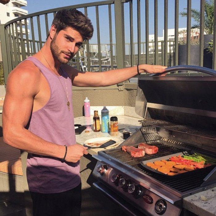 Hombre guapo cocinando carne asada