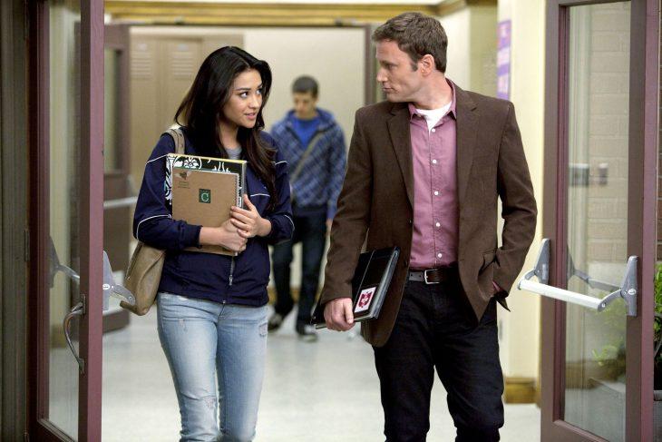 Escena de la serie pretty little liars chica caminando junto a un maestro