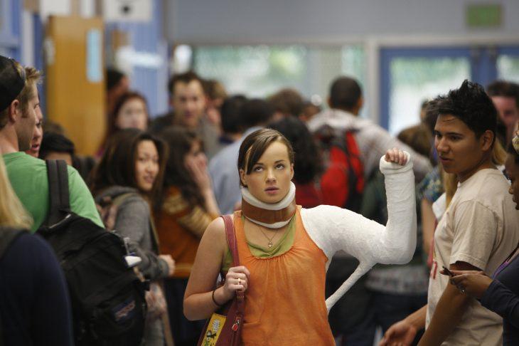 Escena de la serie that girl chica con el brazo quebrado caminando por los pasillos de una escuela
