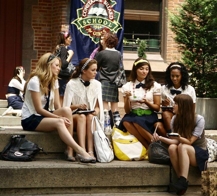 Escena de la serie gossip girls chicas sentadas fuera de la escuela conversando
