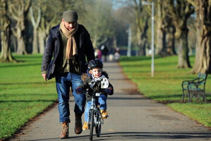 Papá cuida a su hijo que pasea en bicicleta