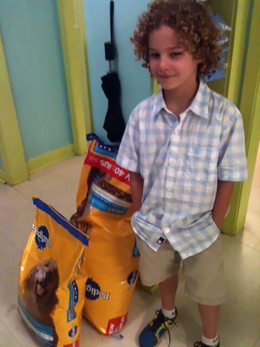 Niño que dono alimento para perros de un refugio