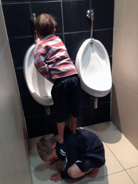 Niño apoyando a otro para que pueda ir al baño