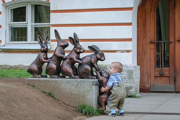 Niño ayudando a un conejo estatua a subir a la sima