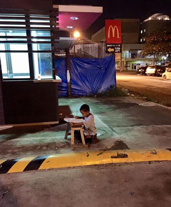 Niño sin hogar hace su tarea con la luz de un local