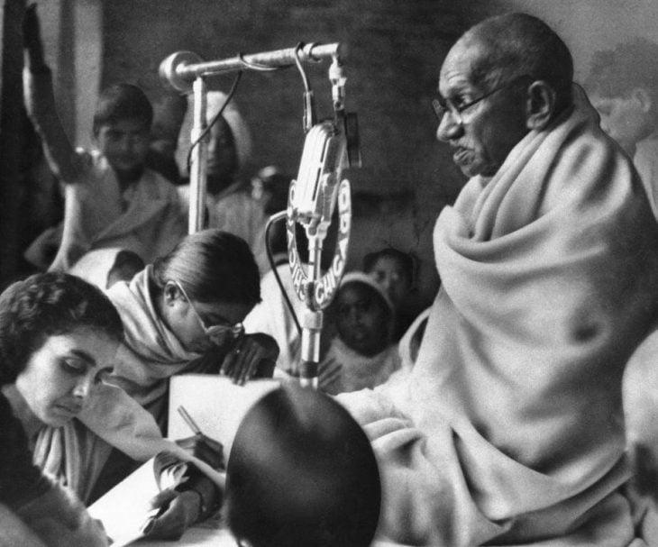 Gandhi sentado con personas escribiendo