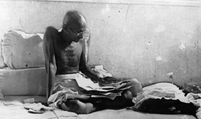 Gandhi sentado en el piso