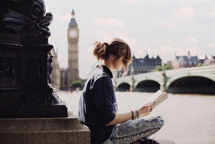 Chica leyendo en la calle