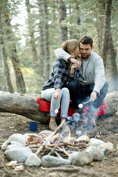 Pareja de novios asando malvaviscos en un campamento
