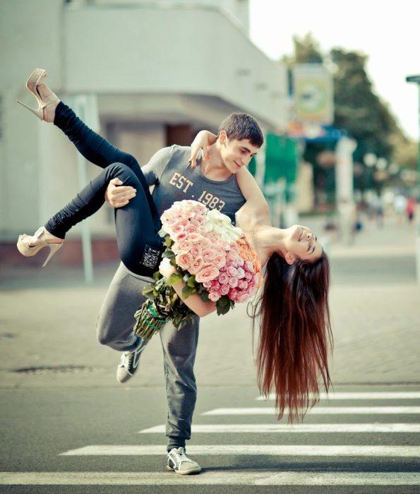 Chico cargando a una chica que trae en sus manos un ramo de rosas