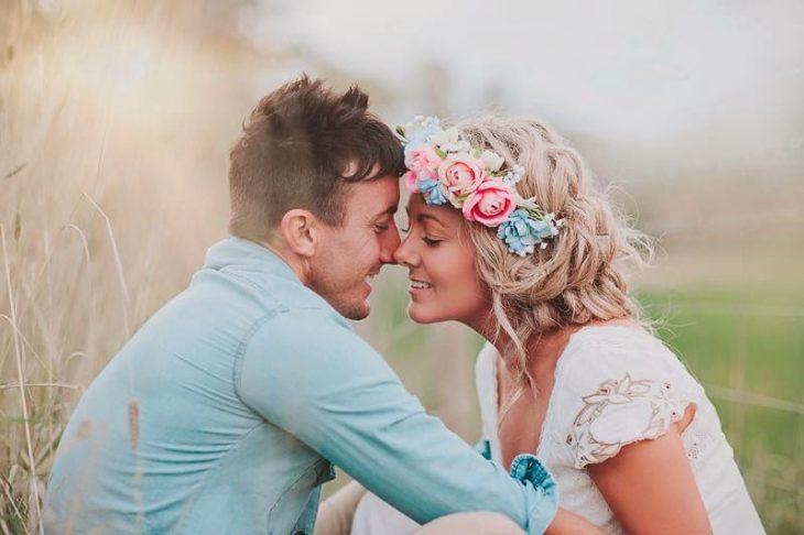 Chico besando a una chica en la mejilla mientras están sentados en el césped