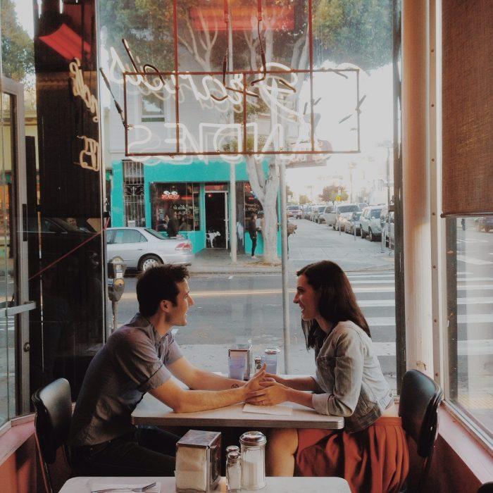 Pareja de novios conversando mientras están en un café