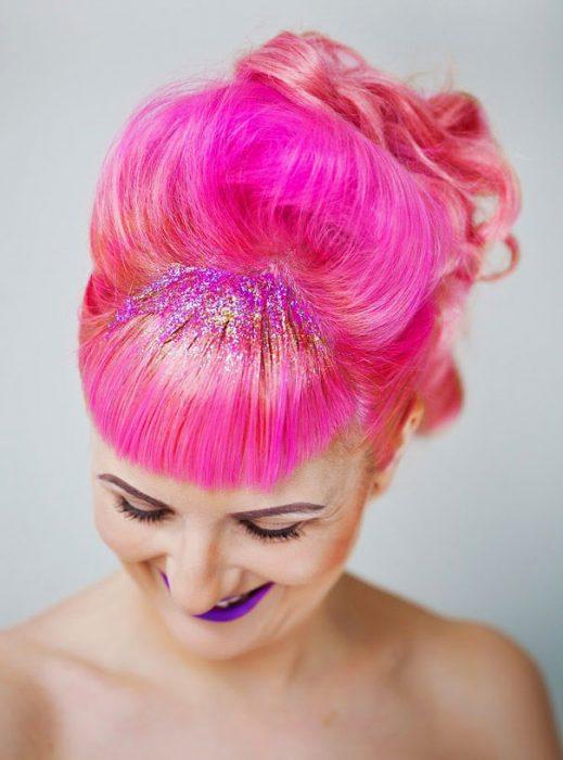 Chica con el cabello rosa y con brillos rosa y naranja en el copete