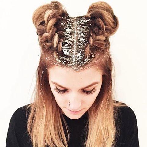 Chica con dos trenzas en su cabello y brillos color plata cubriendo su raíz