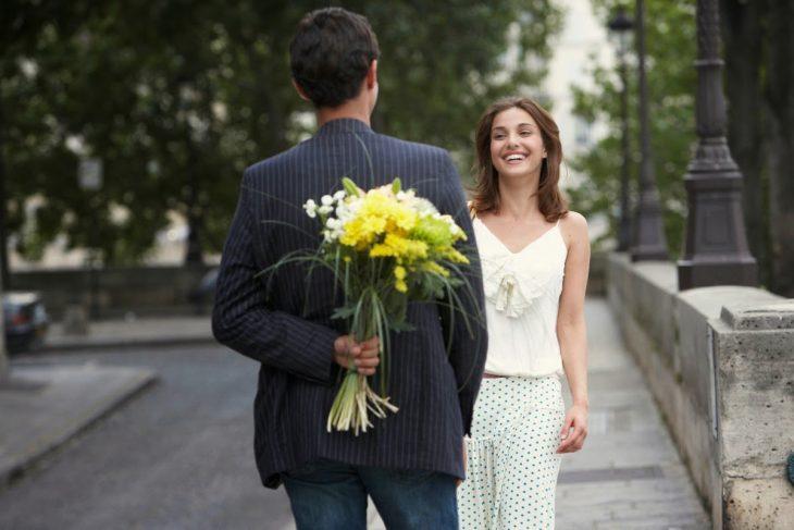 Hombre oculta ramo de flores a chica que sonríe