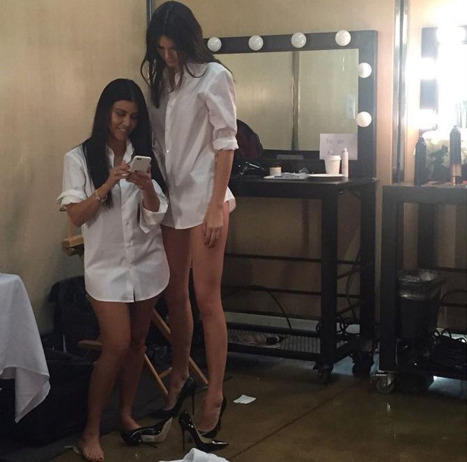 Kendall jenner parada junto a kourtney kardashian viendo el celular