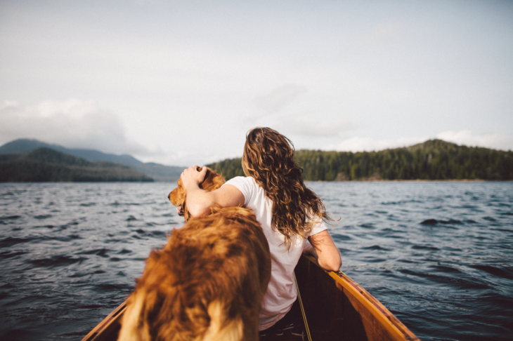 Chica en una lancha con su perro