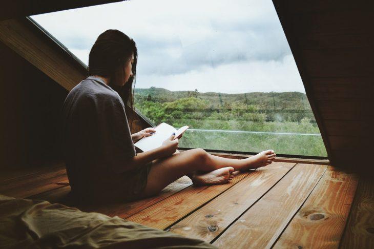 Chica frente a una ventana leyendo
