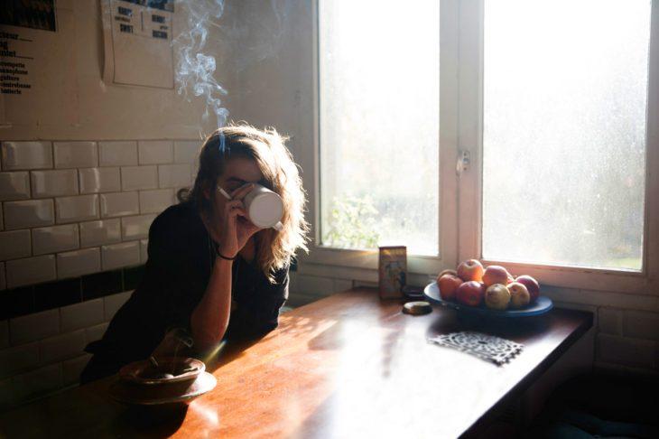 Chica tomando un café y fumando un cigarro