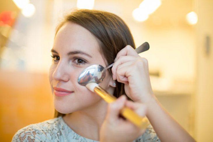 Chica contorneando sus mejillas con la ayuda de una cuchara