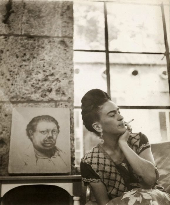 Frida Kahlo frente a un autorretrato de Diego rivera. Fotografía de Manuel Alvarez Bravo