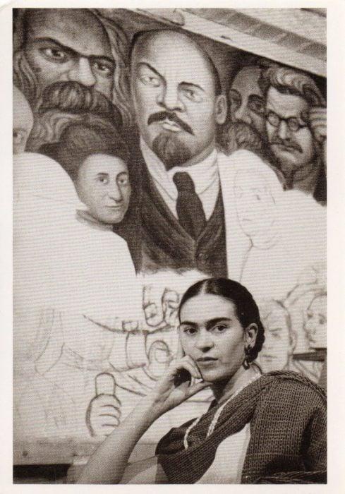Frida Kahlo sentada frente a un mural de Diego Rivera