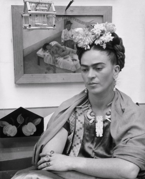 Frida Kahlo sentada frente a uno de sus cuadros en 1945