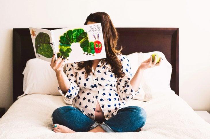 Sesión de fotos de maternidad chica leyendo un libro a su bebé mientras está sentada en la cama