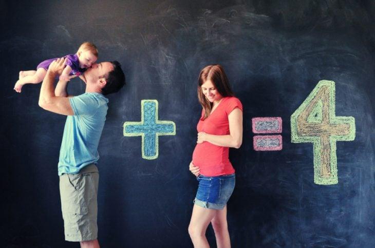 Sesión de fotos de maternidad familia haciendo una suma que da 4