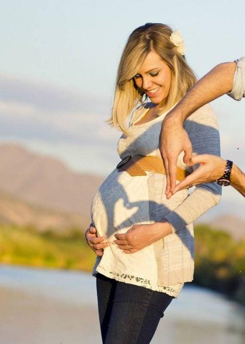 Sesión de fotos de maternidad hombre haciendo un corazón sobre el vientre de una mujer