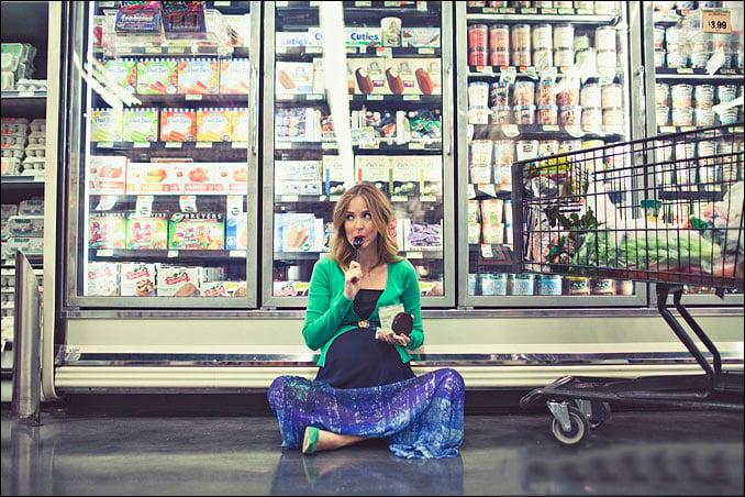 Sesión de fotos de maternidad chica sentada en un supermercado comiendo nieve