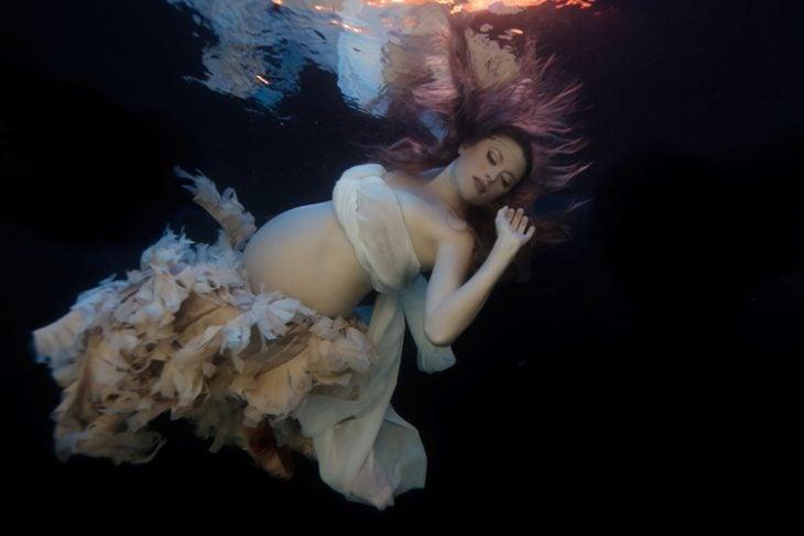 sesión de fotos de maternidad chica bajo el agua mostrando su vientre