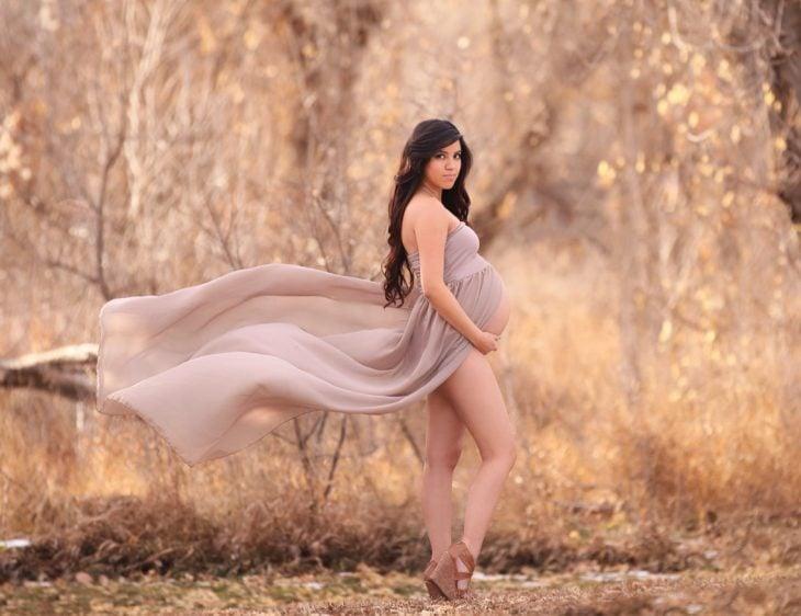 sesiòn de fotos de maternidad chica en un bosque con un vestido mostrando su vientre